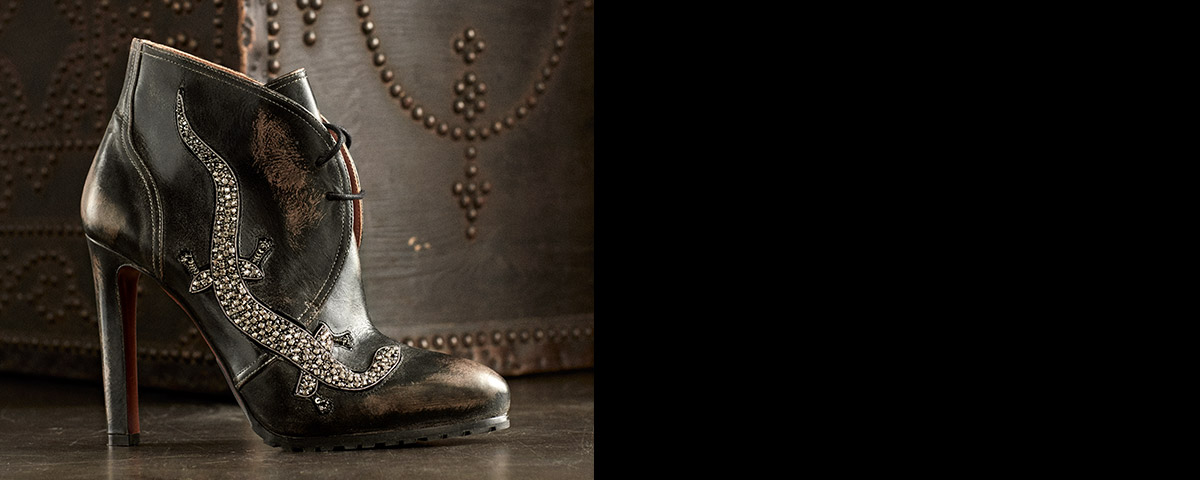 High-heeled leather bootie with a crystal gecko at the side.
