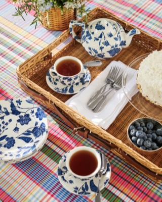 Tea setting in wicker serving tray on madras tablecloth
