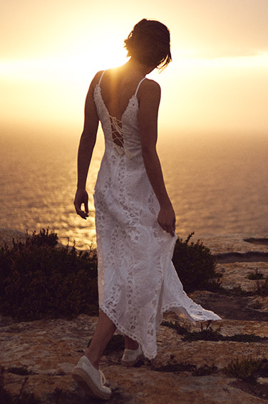 Woman on beach in white eyelet-embroidered spaghetti-strap dress