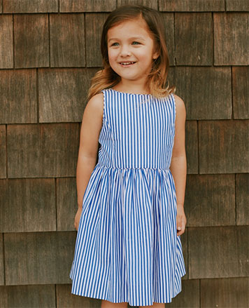 Girl wears blue-and-white bengal-stripe dress.