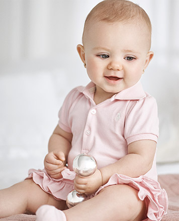 Baby girl wears pink Polo dress.