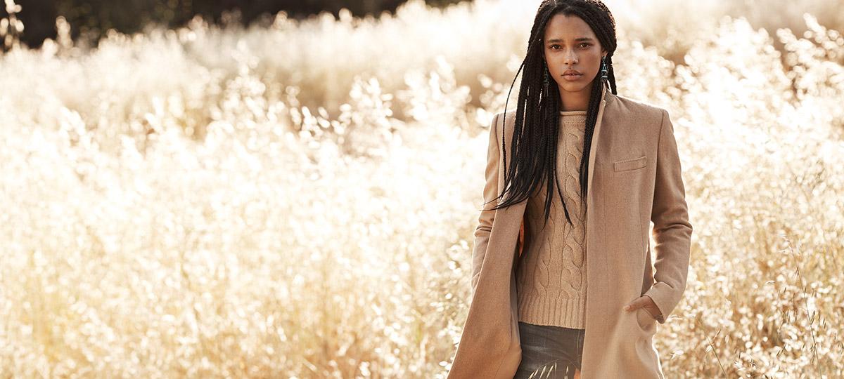 Woman in camel-hair coat in field