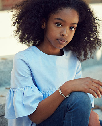 Girl wears light-blue shirt with ruffled sleeves and jeans.