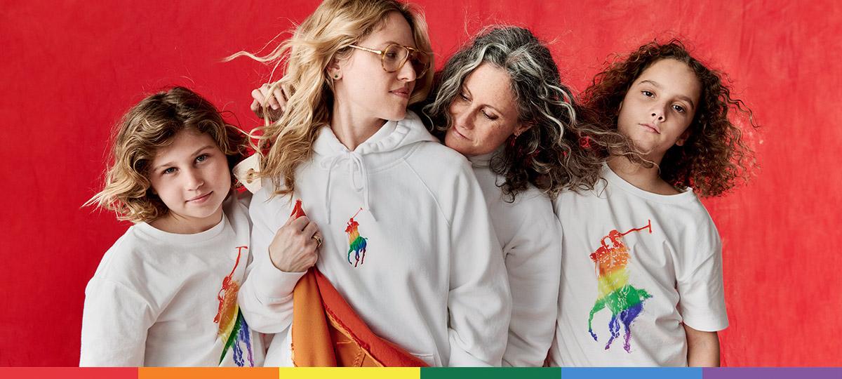 Women and children wear white tees and sweatshirts with rainbow ponies at the chest.