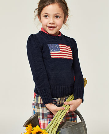 Girl wears American flag sweater with madras shorts.
