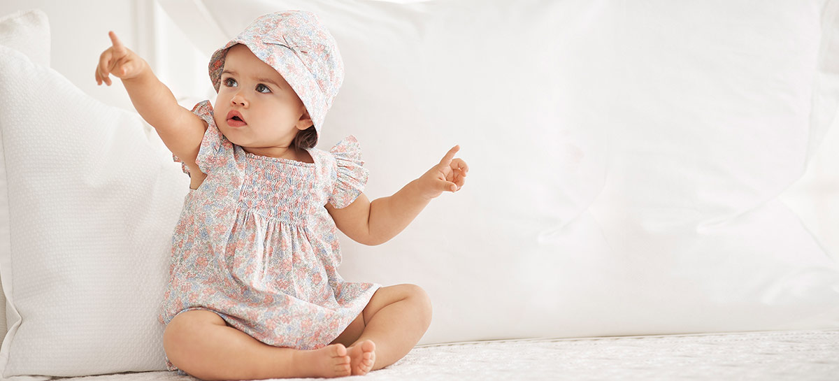 Baby girl wears floral-print dress and hat. 58bbaa213d68