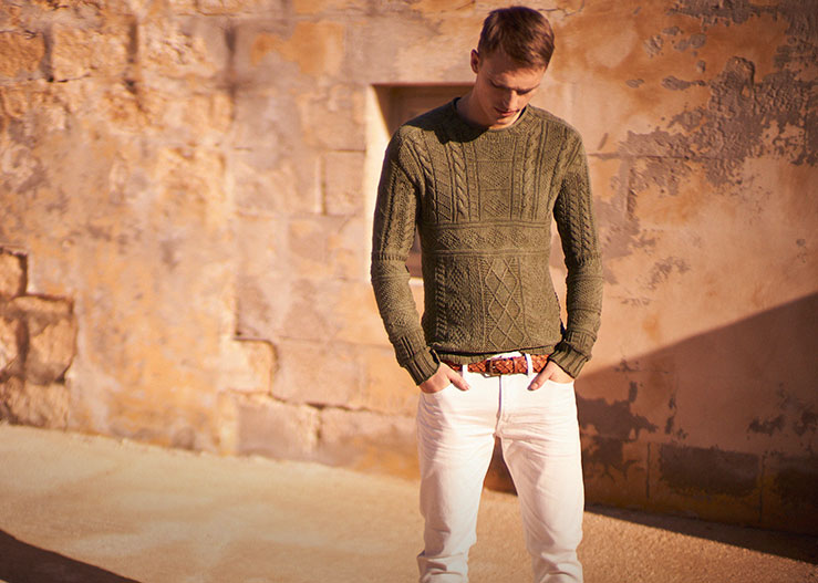 Man in olive-hued sweater with cable & crisscross designs