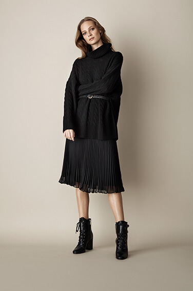 Woman in black pleated skirt