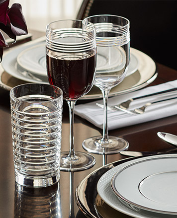Table set with white plates and various glasses.