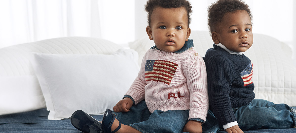Baby boy and girl wear American flag sweaters and jeans.