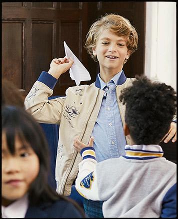 Boy wearing bomber jacket throws paper airplane.