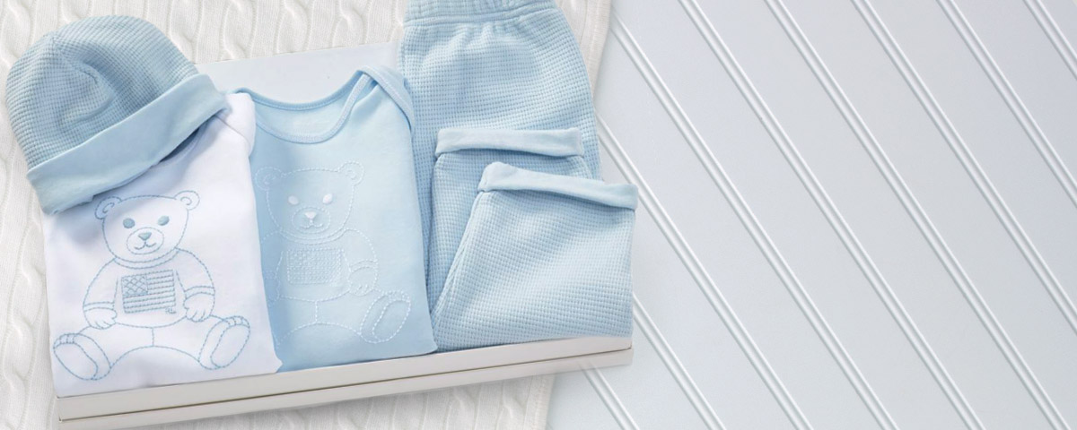 Gift set of baby apparel in light blue and white.