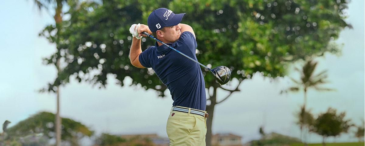 Justin Thomas swinging golf club on the green