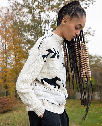 Woman in white multi-knit sweater with horse & Southwestern motifs