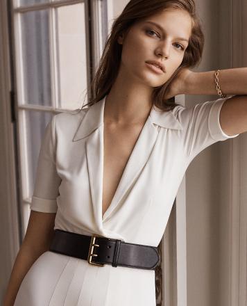 Woman wears belted cream dress