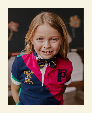 Girl wears color-blocked Polo shirt and bow tie.