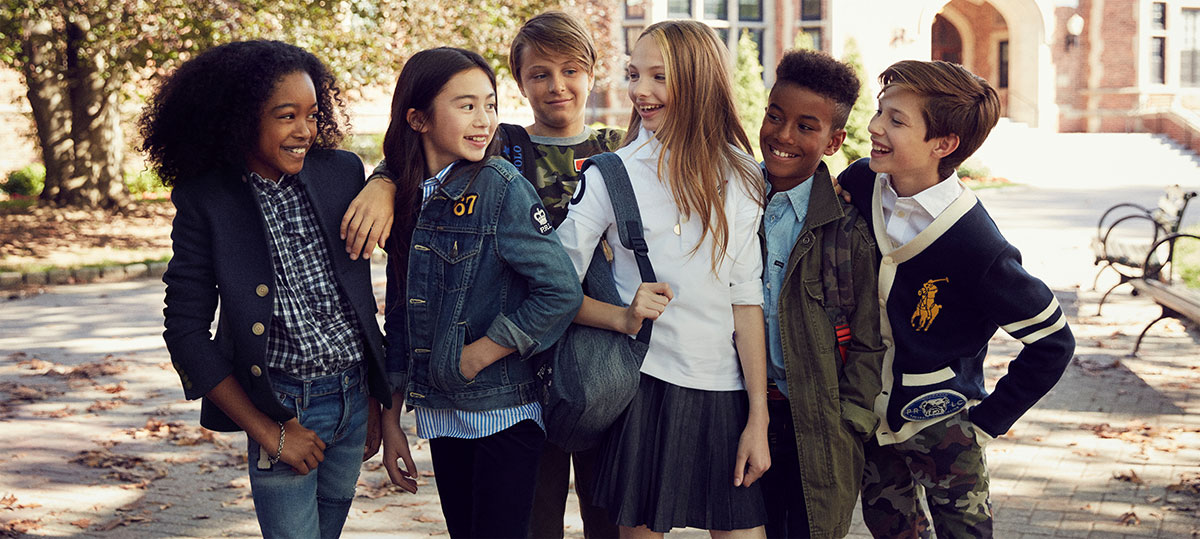 Kids stand outside wearing back-to-school outfits.