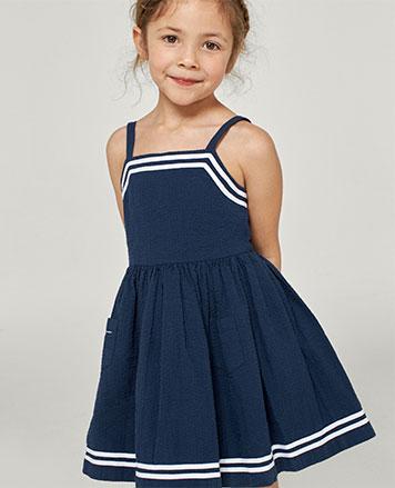 Girl wears navy seersucker dress with white trim.