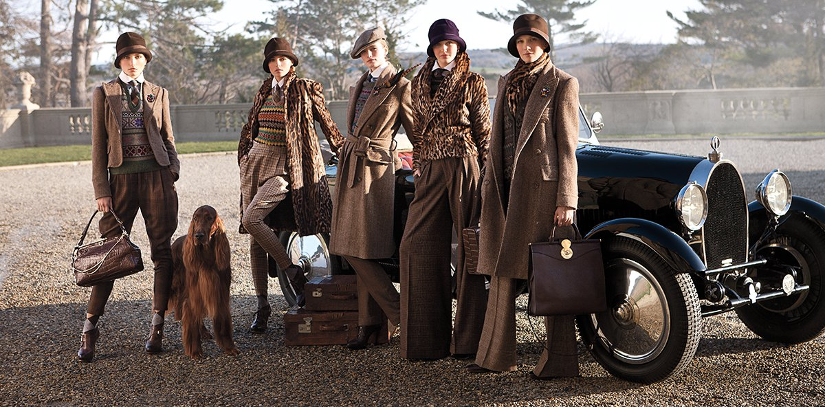Models wear various brown outfits posing in front of old-fashioned car.
