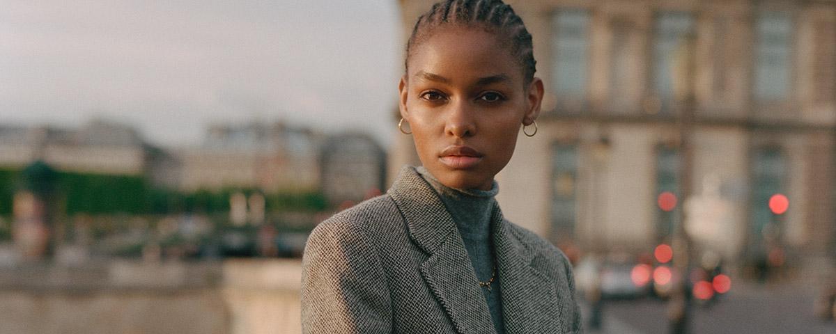 Woman in grey herringbone blazer in city