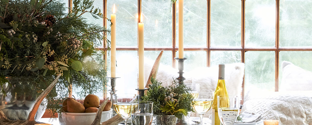 Lit candlesticks in holders on table with  wintry centerpieces