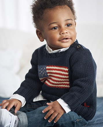 Baby boy wears navy American flag sweater and jeans.