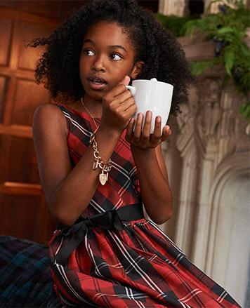 Girl wears tartan dress with sash and holds mug of hot chocolate.