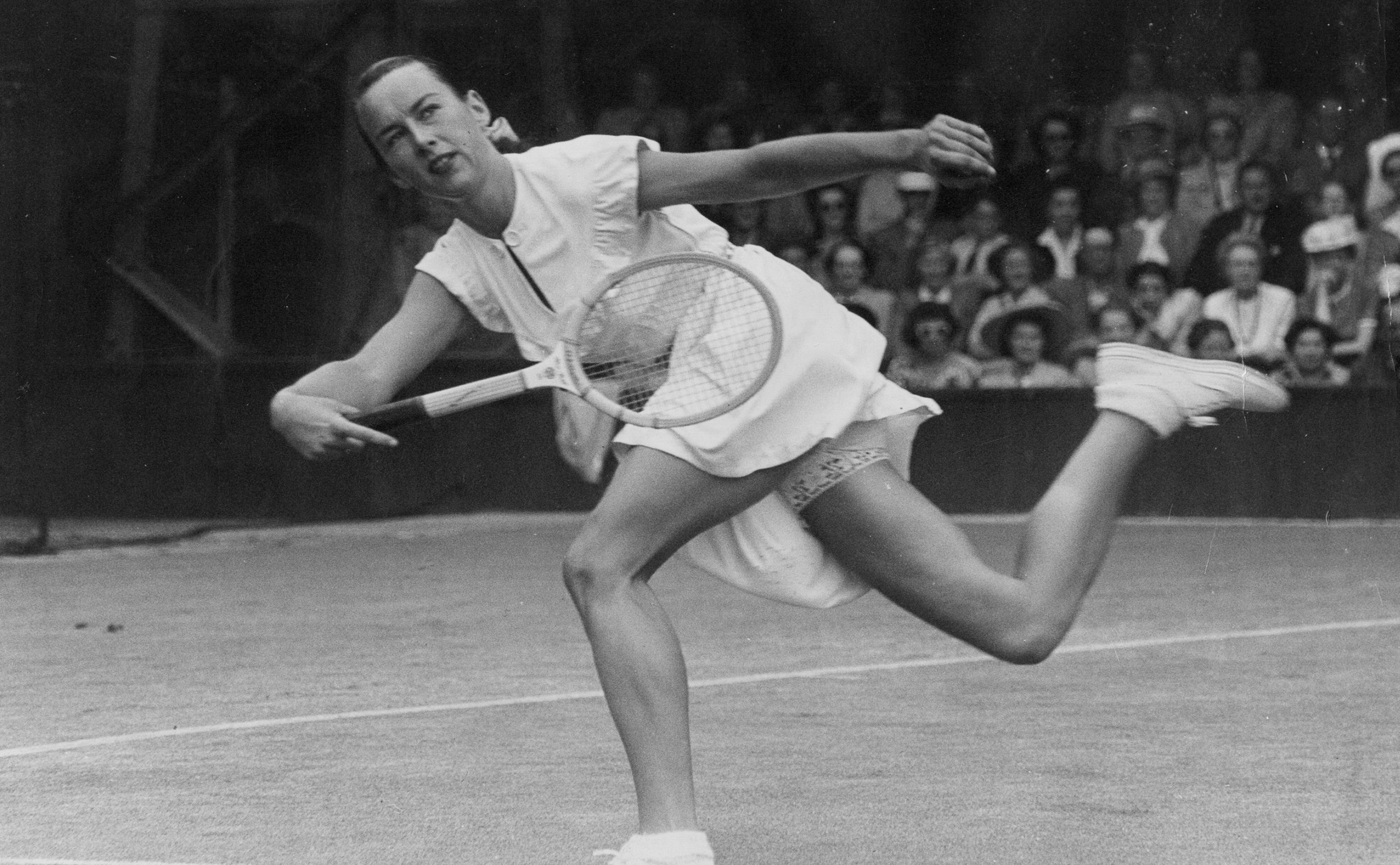 American tennis player Gertrude Moran, or Gorgeous Gussie, on her way to beating F M Wilford at Wimbledon in 1949