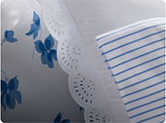 Lace-trim white pillow & sheeting with blue stripes & florals.