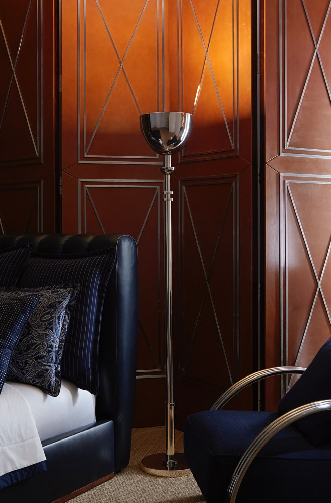 Tall stainless steel lamp in Art Deco-inspired room.