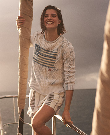 Woman on sailboat in American flag sweater with indigo-dyed details