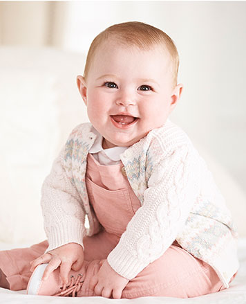 Baby girl wears white cable-knit cardigan over pink overalls.