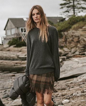 Woman in fringe plaid skirt