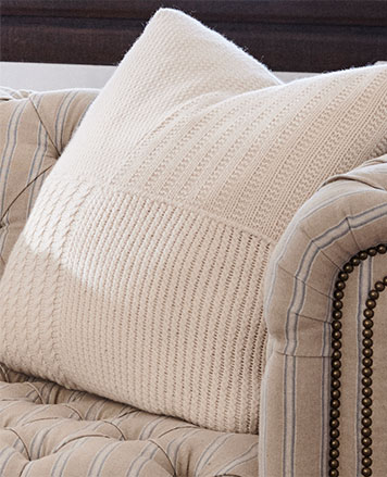 Cream-hued throw pillow with contrast knits