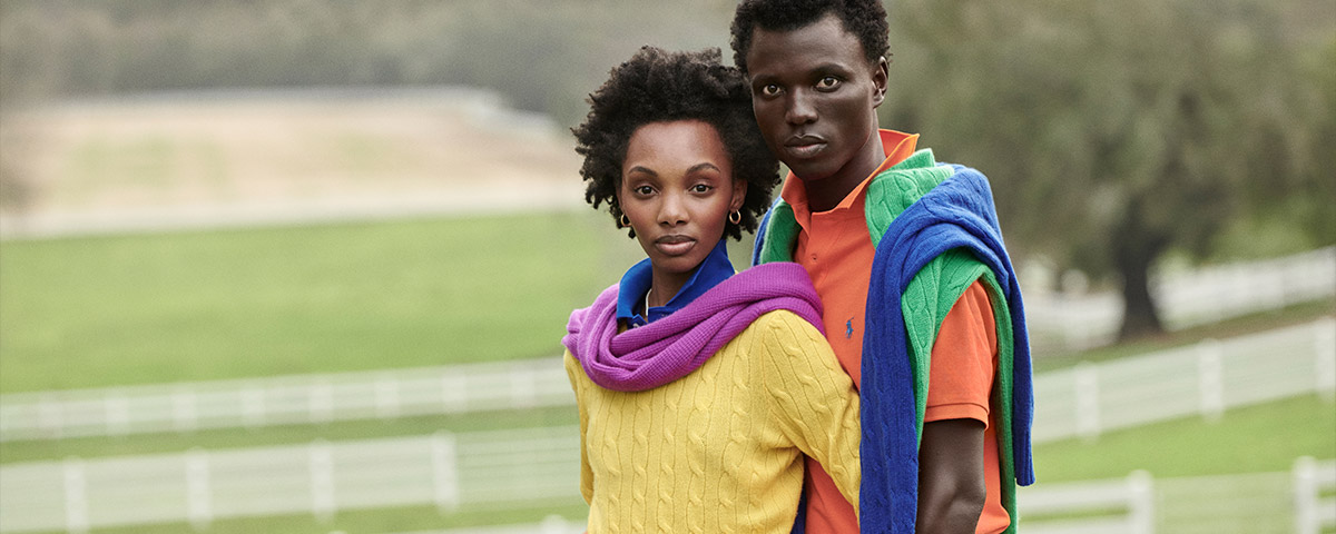 Man & woman modeling bright yellow, green & blue cable knits
