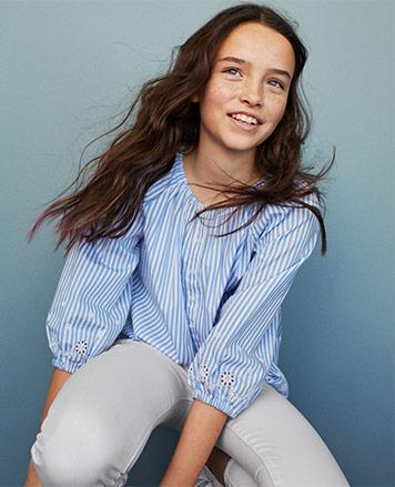 Girl wears seersucker shirt and white pants.