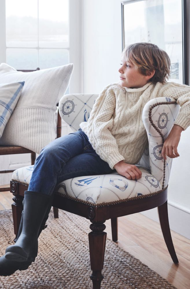 Boy sitting in accent chair with nautical-inspired pattern.