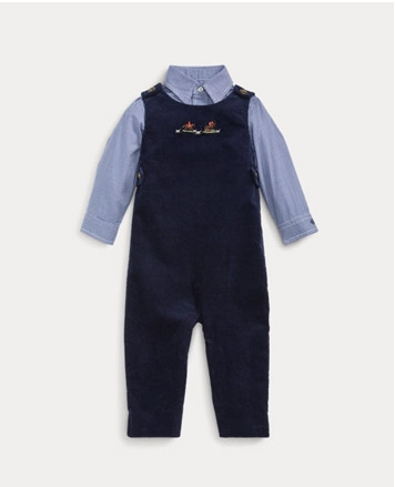 Navy overalls over blue button-down shirt.