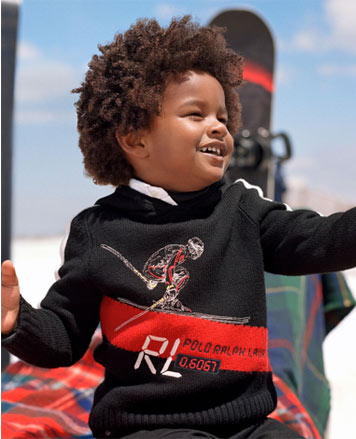 Boy wears black sweater with skier graphic at front.