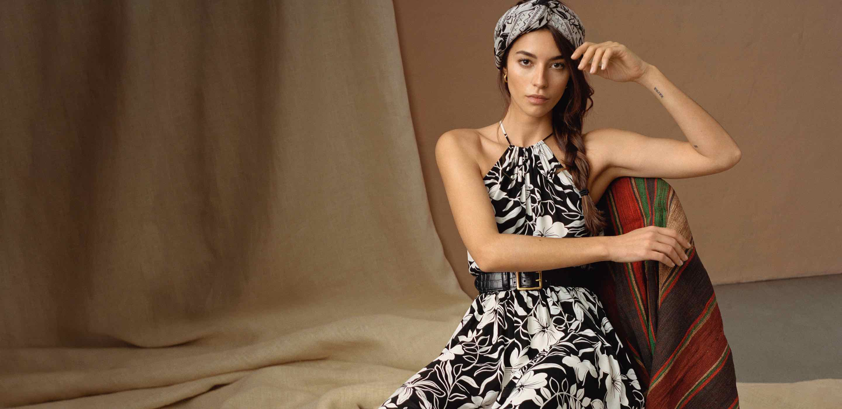 Woman wears black-and-white floral halter dress.