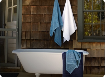 Blue & white towels hanging on wall above footed white bathtub.