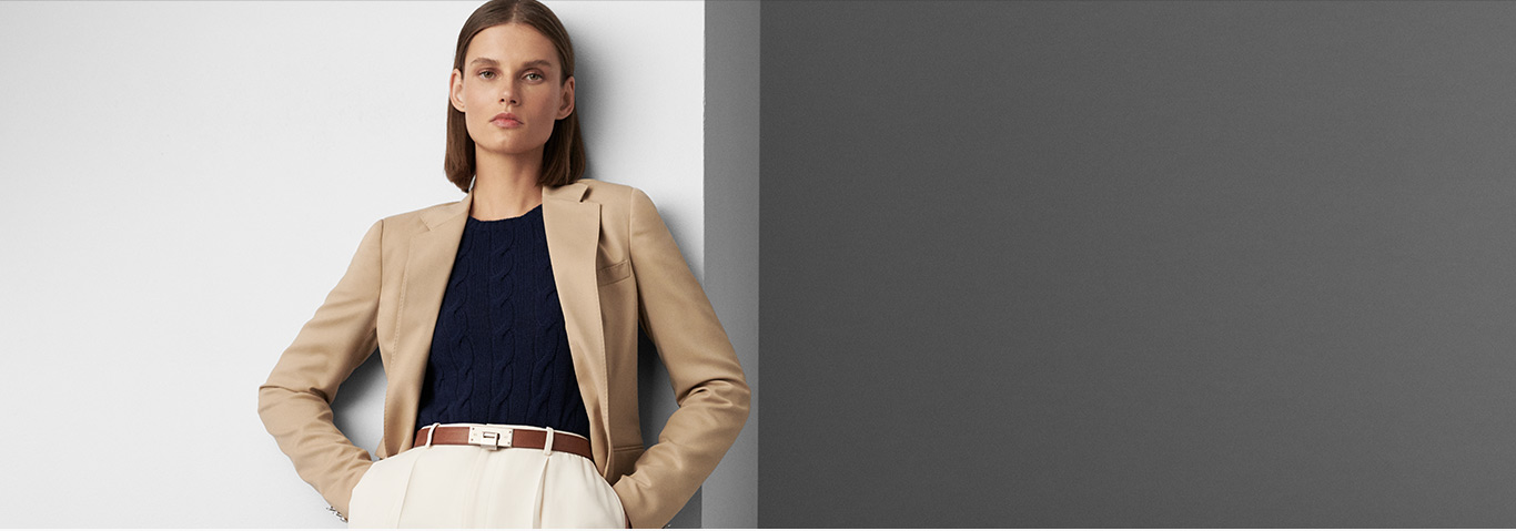 Woman in sleek tan blazer, slim cable sweater & white trousers