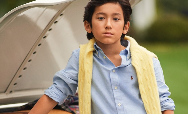 Boy wears blue button-down shirt with yellow sweater over shoulders.