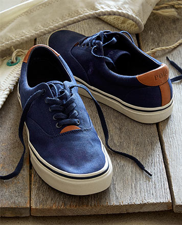 Blue canvas sneakers with tan leather trim