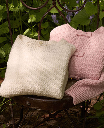 Seed-stitched bow-back sweaters in cream and pale pink.