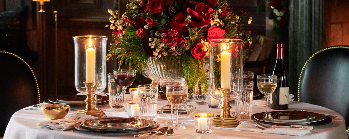 Table set with wine & water glasses, festive plates & candles