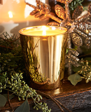 Candle in gold-tone glass vessel