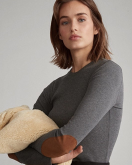 Model wearing grey knit top with brown leather elbow patches