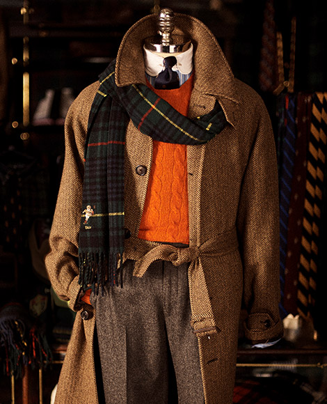 Tan herringbone coat paired with plaid scarf with Kicker Bear accent