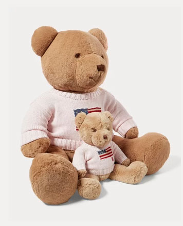 Large and small stuffed bears wearing pink American flag sweaters.